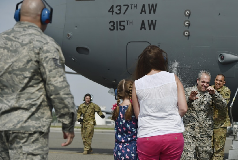 Chief Master Sgt. Kristopher Berg, 437th Airlift Wing command chief, is sprayed down with water by his wife, Amy, and 8 year old daughter, Bella, during his final flight at Joint Base Charleston, S.C., May 11, 2017. Airmen and civilians were present to congratulate him during the event.