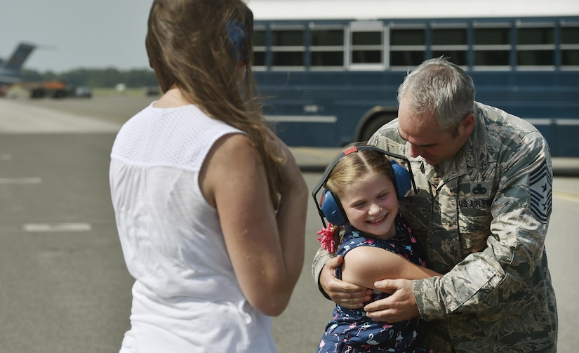 Chief Master Sgt. Kristopher Berg, right, 437th Airlift Wing command chief, hugs his 8 year old daughter, Bella, during his final flight at Joint Base Charleston, S.C., May 11, 2017. His wife, Amy, left, Airmen and civilians were present to congratulate him during the event.