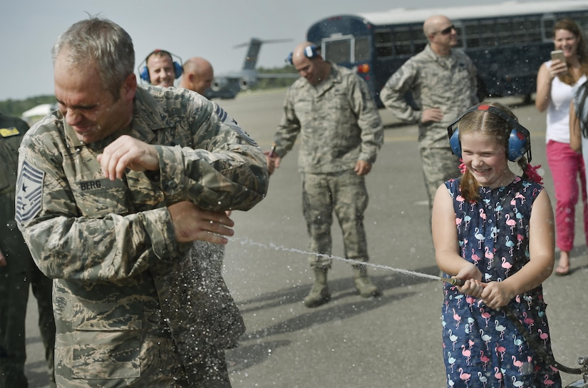 Bella Berg, right, 8 years old, sprays down her father, Chief Master Sgt. Kristopher Berg, left, 437th Airlift Wing command chief, during his final flight at Joint Base Charleston, S.C., May 11, 2017. His wife, Amy, Airmen and civilians were also present to congratulate him during the event.