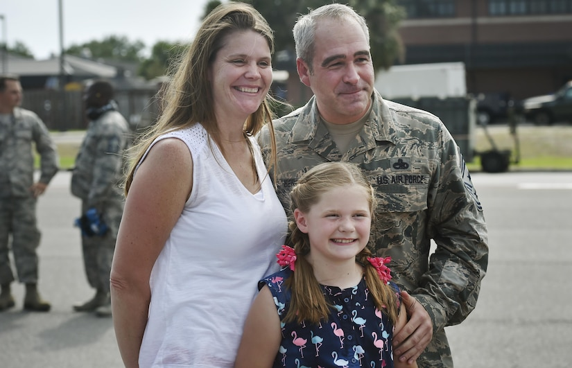 Chief Master Sgt. Kristopher Berg, right, 437th Airlift Wing command chief, poses for a photo with his wife, Amy, left, and 8 year old daughter, Bella, center, during his final flight at Joint Base Charleston, S.C., May 11, 2017. Airmen and civilians were also present to congratulate him during the event. (U.S. Air Force photo by Staff Sgt. Christopher Hubenthal)