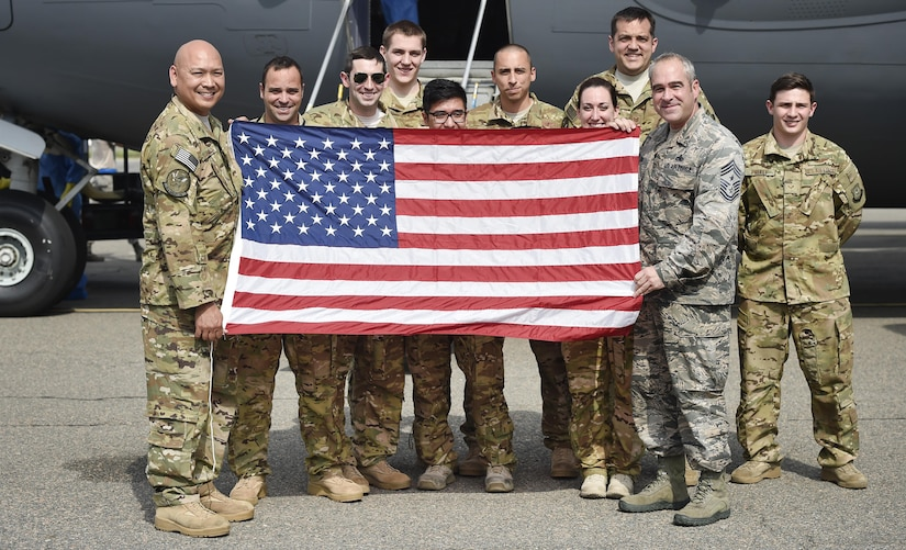 Chief Master Sgt. Kristopher Berg, right, 437th Airlift Wing command chief, poses for a photo with Col. Jimmy Canlas, 437th AW commander, and Airmen of the 437th AW during his final flight at Joint Base Charleston, S.C., May 11, 2017. His wife, Amy, 8 year old daughter, Bella, Airmen and civilians were also present to congratulate him during the event.