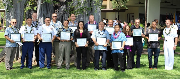 Fifteen Defense Logistics Agency Pacific awardees stand with DLA Pacific Commander Navy Capt. Timothy Daniels at the 61st Annual Excellence in Federal Government Awards held at Hickam Officer's Club, Joint Base Pearl Harbor-Hickam, Hawaii, May 6.