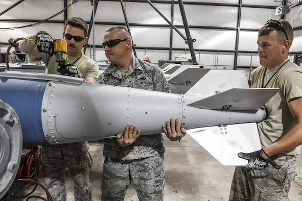 From the left, Senior Airman Steven Woods, Tech. Sgt. Joseph Munis and Senior Airman Zane Sitzes, all active-duty Airmen from the 301st Fighter Wing, Naval Air Station Fort Worth Joint Reserve Base, Texas, build GBU-31 bombs April 26 at Hill Air Force Base, Utah. The 301st FW sent Airmen and F-16 Fighting Falcon aircraft to Hill AFB for Combat Hammer, an air-to-ground weapons evaluation exercise conducted by the 86th Fighter Weapons Squadron.  (U.S. Air Force/Paul Holcomb)