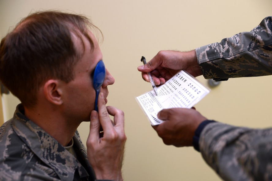 Staff Sgt. William Behl (left), 62nd Maintenances Squadron crewchief, has his eyes examined by Senior Airman Shailesh Kumar, 446th Aerospace Medicine Squadron optometry technician, May 9, 2017, at Joint Base Lewis-McChord, Wash. The clinic provides routine eye exams which includes prescription check and an eye health check. (U.S. Air Force photo/Senior Airman Jacob Jimenez)