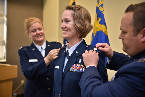 Newly promoted Lt. Col. Marta Davies, 932nd Airlift Wing Operations Group executive officer, has her father's silver oak leaves pinned on with assistance from Maj. Rachelle Amado and Capt. Brent Bettis, both with the 932nd Aeromedical Evacuation Squadron May 6, 2017, Scott Air Force Base, Illinois. (U.S. Air Force photo by Tech. Sgt. Christopher Parr)
