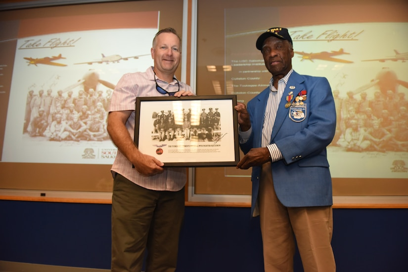 "Retired Air Force Col. Rick Williamson, left, a former pilot and squadron commander at Joint Base Charleston, receives a photograph of the Tuskegee Airmen from retired Lt. Col. Enoch ""Woody"" Woodhouse, right, an original Tuskegee Airman, during a ceremony at the 15th Airlift Squadron auditorium May 11, 2017. Williamson and Woodhouse spoke to attendees of the 2017 Take Flight Aviation Camp and emphasized the importance of education and innovation. The camp is a Science, Technology, Engineering and Mathematics (STEM) program offered to encourage students to be career ready out of high school or college."