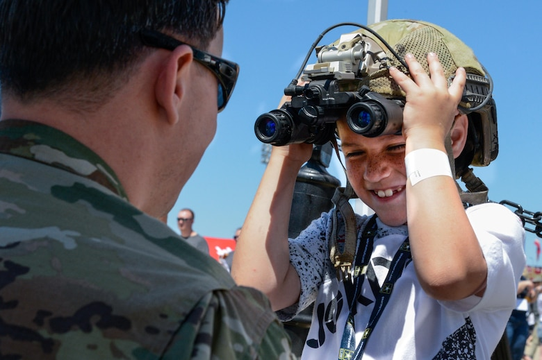 A Tactical Air Control Party Airman interacts with a child during the 2017 Barksdale Air Force Base Airshow, May 6. The show provided a variety of exhibits and demonstrations for the audience. (U.S. Air Force photo/Senior Airman Mozer O. Da Cunha)