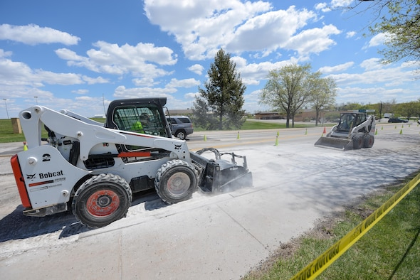 Members of the 55th Civil Engineer Squadron's pavement and equipment team make repairs to SAC Blvd. May 3. Their 14-man crew is responsibility for all road, parking lot and runway repairs along with several other construction jobs. (U.S. Air Force photo by Zach Hada)