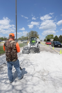 Members of the 55th Civil Engineer Squadron's pavement and equipment team make repairs to SAC Blvd. May 3. Their 14-man crew, in the winter months, are also responsible for snow removal.  (U.S. Air Force photo by Zach Hada)