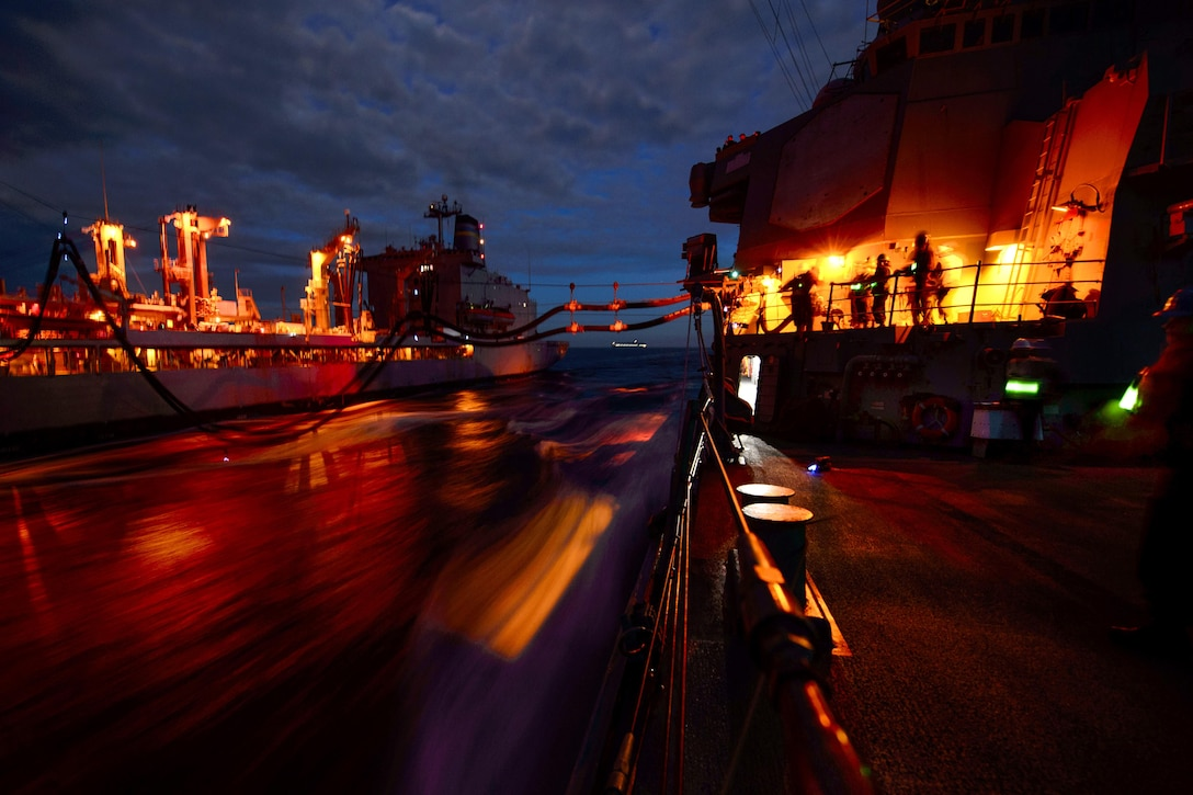 The USS Fitzgerald a conducts a night replenishment at sea.