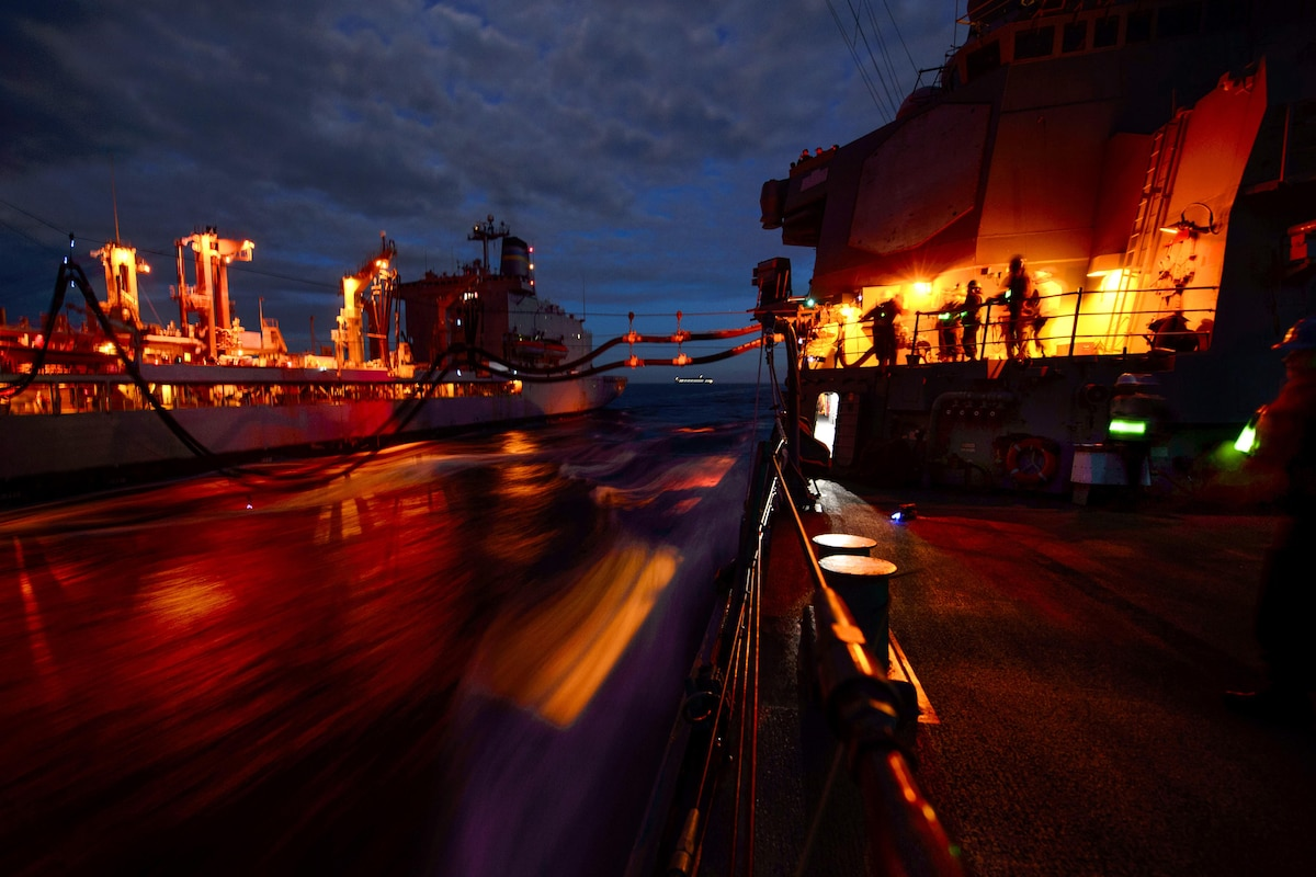 Two ships conduct a night replenishment at sea as yellow lights flare.
