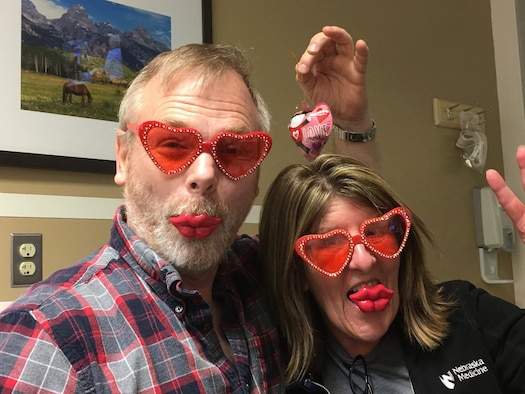 Ken Bauer, 55th Wing Plans, Program and Requirements office international program officer and senior technical advisor with the 55th Wing Plans, Program and Requirements office enjoy heart-shaped sunglasses and treats for Valentine's Day with Diane Cox, Nebraska Medical Center nurse in Omaha, Nebraska. Bauer, a cancer patient, has used the idea for wearing costumes to chemotherapy to keep fellow patients and staff in good spirits. (Courtesy Photo)