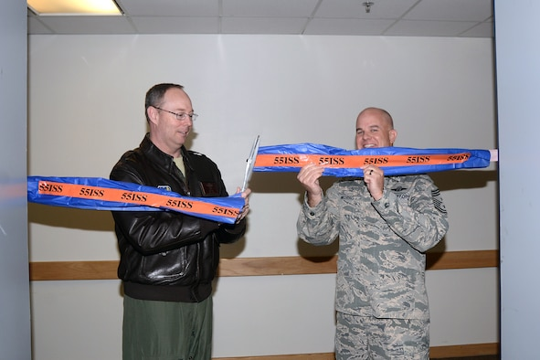 Col. David Berg, 55th Wing vice commander, and Chief Master Sgt. Michael Morris, 55th Wing command chief, cut the ribbon on the 55th Wing Operations Center during a ribbon cutting ceremony at the 55th Intelligence Support Squadron May 1. The WOC is now the central hub for wing-level situational awareness on all of its intelligence, surveillance and reconnaissance assets, as well as its electronic warfare assets, supporting combatant commanders around the world on a daily basis. (U.S. Air Force photo by Kendra Williams)