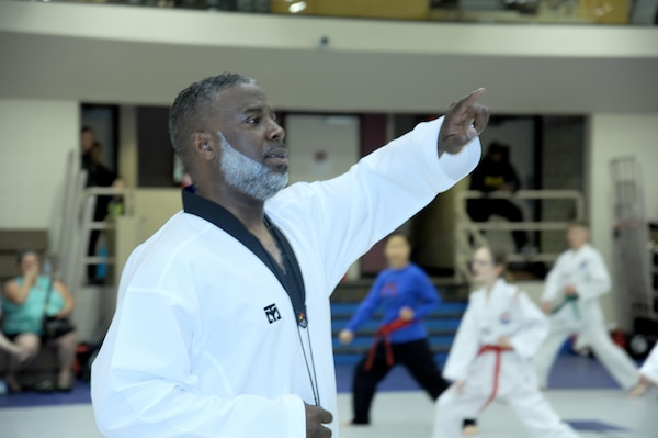 Jeffrey Davis, an emergency management specialist with the U.S. Army Engineering and Support Center, Huntsville, and taekwondo black belt master, leads students through various martial arts techniques and exercises.
