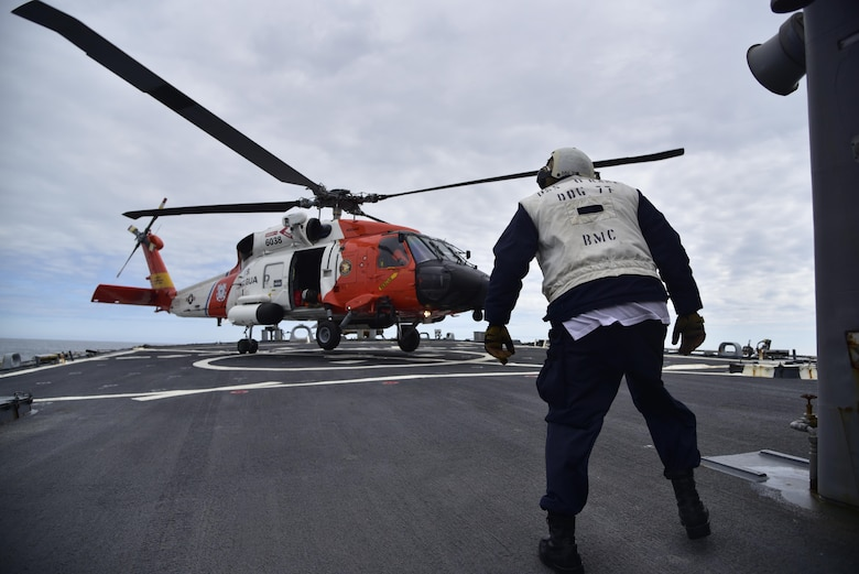 A Chief Boatswain's Mate assigned to Arleigh Burke-class guided missile destroyer USS O'Kane (DDG 77) observes a U.S. Coast Guard MH-60T Jayhawk helicopter assigned to Air Station Kodiak, Alaska, landing during flight deck operations in the Gulf of Alaska. Northern Edge 2017 is Alaska's premiere joint-training exercise designed to practice operations, techniques, and procedures as well as enhance interoperability among the services. Thousands of participants from all the services; Sailors, Soldiers, Airmen, Marines, and Coast Guard personnel from active duty, Reserve and National Guard units, are involved.