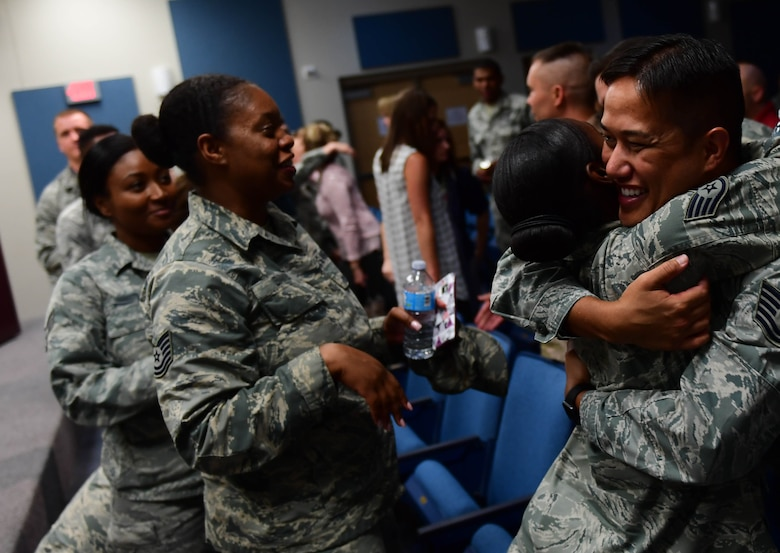 Airmen give Tech. Sgt. Palani, 799th Air Base Squadron NCOIC of vehicle operations, a hug after the first Storytellers event May 10, 2017, at Creech Air Force Base, Nev. Palani shared his experiences as a child and overcoming the adversity of having a drug-addicted father and survived molestation as a child. (U.S. Air Force photo/Senior Airman Christian Clausen)