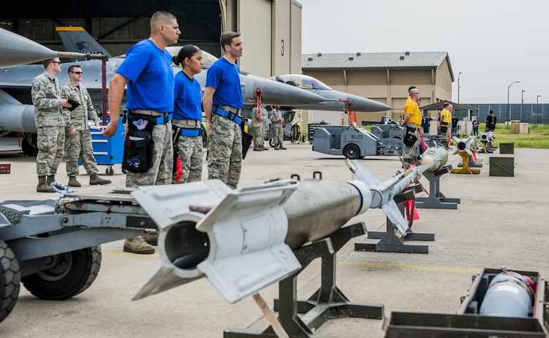 U.S. Air Force Airmen from the 35th, 14th, and 80th Aircraft Maintenance Units stand in front of three F-16 Fighting Falcons before the start of the 2017 annual weapons load crew competition at Kunsan Air Base, Republic of Korea, May 13, 2017. The annual load competition tests objectives like safety, speed, and cleanliness to enhance PACAF's and ROKAF's mission of always being ready to fight tonight. (U.S. Air Force photo by Senior Airman Colville McFee/Released)