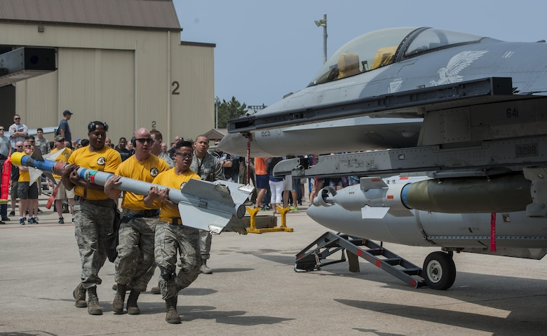 U.S. Air Force load crew members from Misawa Air Base carry a bomb toward an F-16 Fighting Falcon while an evaluator observes during the 2017 annual weapons load crew competition at Kunsan Air Base, Republic of Korea, May 13, 2017.  Kunsan, Osan, and Misawa Air Base Airmen participated in this year's weapons load competition, making it one of the largest weapons load competitions ever hosted by Kunsan. (U.S. Air Force photo by Senior Airman Colville McFee/Released)