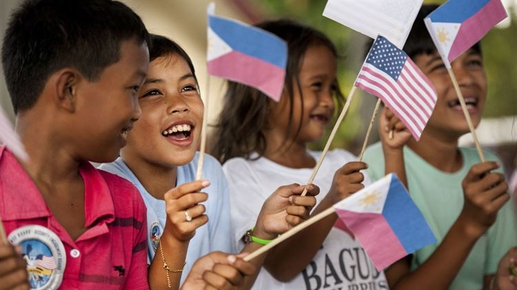 Filipino children wave U.S. and Philippine flags during a groundbreaking ceremony for Balikatan 2017 in Ormoc City, Leyte, April 25, 2017. Leaders from the Armed Forces of the Philippines, U.S. military, and Ormoc City gathered to commemorate the beginning of engineering projects for new classrooms at Margen Elementary School in Ormoc City. Balikatan is an annual U.S.-Philippine military bilateral exercise focused on a variety of missions, including humanitarian assistance and disaster relief and counterterrorism.