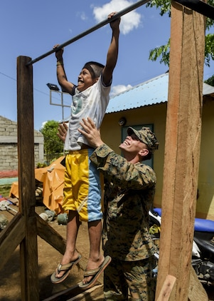 U.S. Marine Lance Cpl. Thomas Whitworth helps a Filipino boy with chin ups during a groundbreaking ceremony for Balikatan 2017 in Ormoc City, Leyte, April 25, 2017. Leaders from the Armed Forces of the Philippines, U.S. military, and Ormoc City gathered to commemorate the beginning of engineering projects for new classrooms at Don Carlos Elementary School in Ormoc City. Balikatan is an annual U.S.-Philippine military bilateral exercise focused on a variety of missions, including humanitarian assistance and disaster relief and counterterrorism. (U.S. Air Force photo by Staff Sgt. Peter Reft)