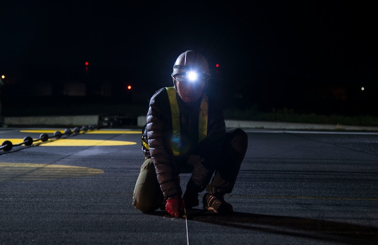 A Japanese contractor with Nippo Corporation holds down a chalk line to make a mark on the runway at Misawa Air Base, Japan, May 5, 2017. More than 50 contracted workers flooded the flightline Wednesday night to tear up the runway, preparing for more than 48,000 feet of flightline to be repaired during a two-month long project. (U.S. Air Force photo by Senior Airman Brittany A. Chase)