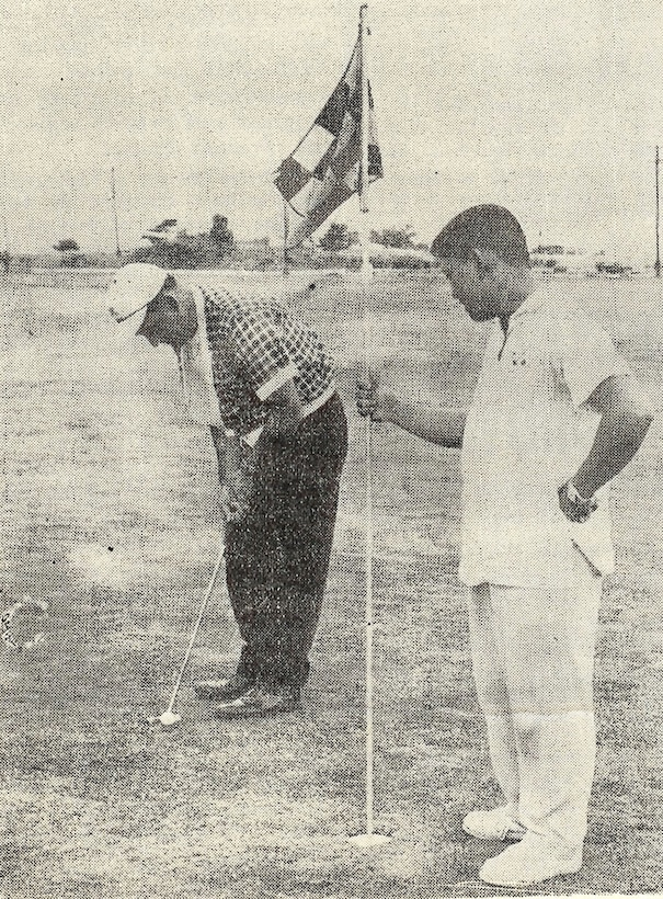 """Tatsuo """"Jimmy"""" Schwartz holds a flag for a golfer at Kadena Air Base, Japan. Shwartz has donated more than 3,300 trees to Kadena over the course of his more than 50 years of service to the U.S. military. (courtesy photo)"""