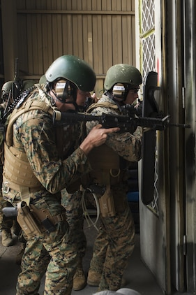 U.S. Marine Corps Lance Cpls. Jackson Stumb, left, and Benjamin Irish, right, Special Reaction Team (SRT) members for Marine Corps Air Station (MCAS) Iwakuni, conduct breaching techniques during cross training exercises with the Hiroshima and Yamaguchi Prefectural Police Headquarters at MCAS Iwakuni, Japan, March 28, 2017. Members with the Hiroshima and Yamaguchi Prefectural Police Headquarters traveled to the air station to observe SRT conduct high-risk training scenarios. The training ranged from room-clearing, breaching, communication and non-lethal take-down techniques. (U.S. Marine Corps photo by Lance Cpl. Joseph Abrego)