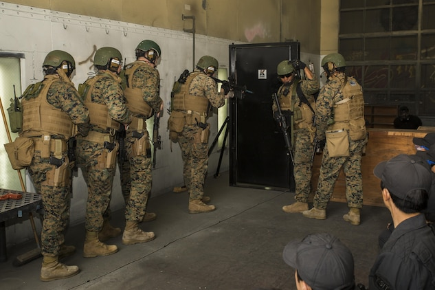 U.S. Marines with the Special Reaction Team (SRT) for Marine Corps Air Station Iwakuni (MCAS), display breaching techniques to members of the Hiroshima and Yamaguchi Prefectural Police Headquarters at MCAS Iwakuni, Japan, March 28, 2017. Members with the Hiroshima and Yamaguchi Prefectural Police Headquarters traveled to the air station to observe SRT conduct high-risk training scenarios. The training ranged from room-clearing, breaching, communication and non-lethal take-down techniques. (U.S. Marine Corps photo by Lance Cpl. Joseph Abrego)