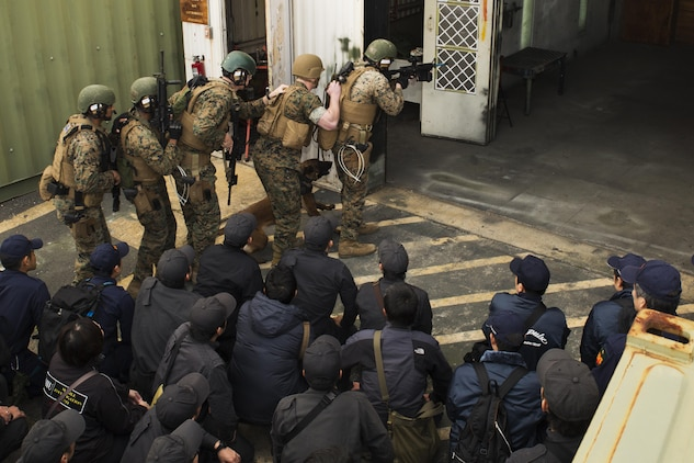 U.S. Marines with the Special Reaction Team (SRT) for Marine Corps Air Station Iwakuni (MCAS), display room-clearing techniques using a military working dog to members of the Hiroshima  and Yamaguchi Prefectural Police Headquarters at MCAS Iwakuni, Japan, March 28, 2017. Members with the Hiroshima and Yamaguchi Prefectural Police Headquarters traveled to the air station to observe SRT conduct high-risk training scenarios. The training ranged from room-clearing, breaching, communication and non-lethal take-down techniques. (U.S. Marine Corps photo by Lance Cpl. Joseph Abrego)