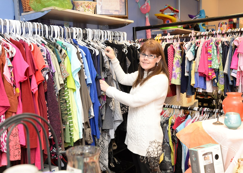 Julie Neilsen, Trader Winston Thrift Shop manager and Mildenhall Spouses' Club member, sorts through the rack of clothes on sale at the store April 27, 2017, on RAF Mildenhall, England. The thrift shop sells a wide variety of used clothes and household items at reduced prices for Airmen and their families. (U.S. Air Force photo by Karen Abeyasekere)
