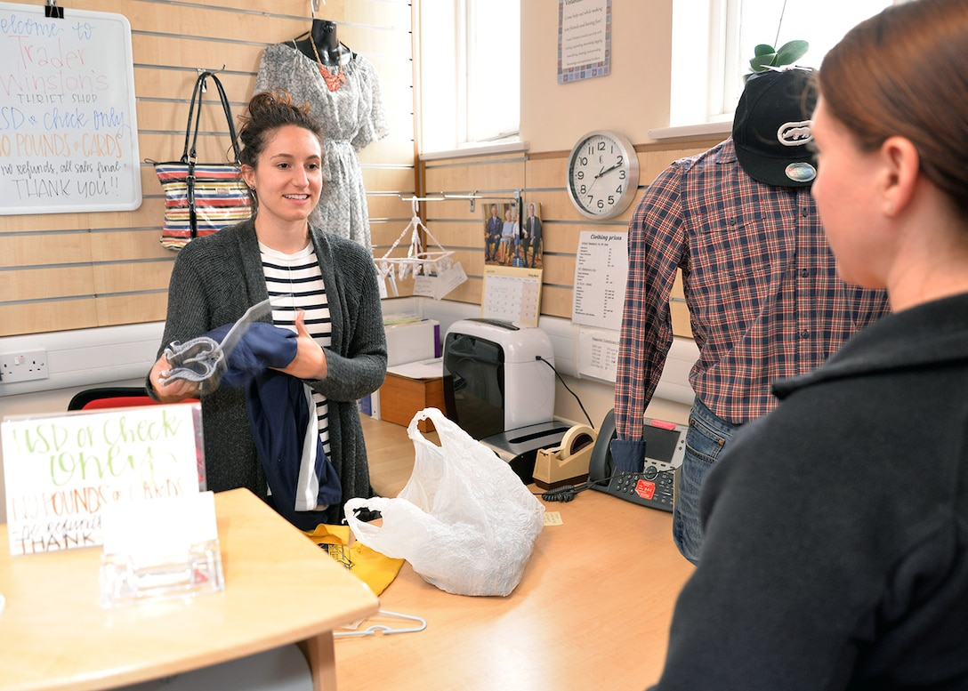 Riley Glowatch, left, Mildenhall Spouses' Club member and Trader Winston Thrift Shop cashier and assistant manager, assists a customer buying childrens' clothes April 27, 2017, on RAF Mildenhall, England. Money raised from items sold in the thrift shop is used to support Department of Defense programs, base morale events and scholarships. (U.S. Air Force photo by Karen Abeyasekere)