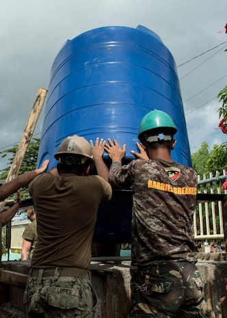 A U.S. Navy Seabee and Philippine Soldier install a water storage tank during an engineering civic assistance project in support of Balikatan 2017 in Ormoc City, Leyte, May 12, 2017. Philippine and U.S. service members worked together to build new classrooms for students at Don Carlos Elementary School. Balikatan is an annual U.S.-Philippine bilateral military exercise focused on a variety of missions, including humanitarian assistance and disaster relief, counterterrorism, and other combined military operations.