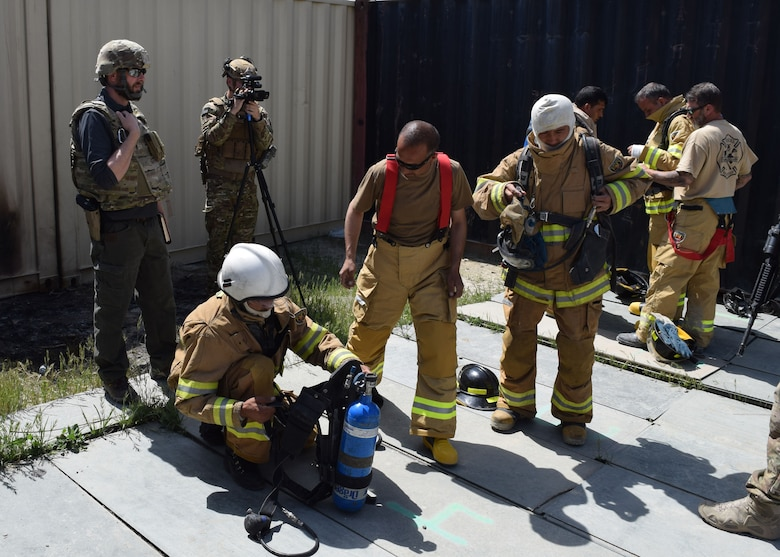 Joshua Mayes (left), 438th Air Expeditionary Wing and Train, Advise, Assist Command – Air (TAAC-Air) historian, observes Afghan firefighters as they don protective gear before entering a burn house May 11, 2017 on Kabul Air Wing. Civil engineer advisors from TAAC-Air routinely work with their Afghan firefighter counterparts to develop a professional, capable and sustainable Air Force. (U.S. Air Force photo by Maj. William Russell)