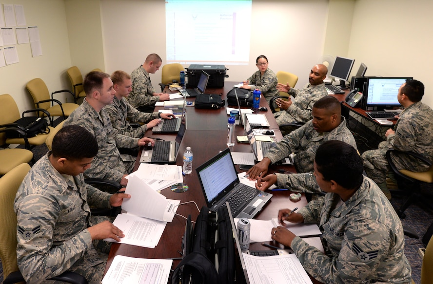 A team of contract specialists and contract officers from the 55th Contracting Squadron discuss learning objectives that were used in various scenarios during a contingency contracting exercise held at Offutt Air Force Base, Neb. May 8 – 12. The exercise was designed to improve contracting readiness for bare base operations. (U.S. Air Force photo by Delanie Stafford)