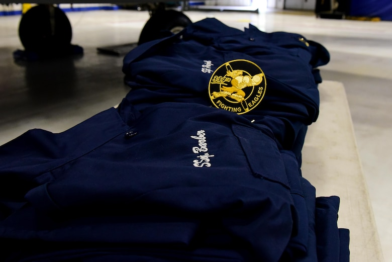 During a Dedicated Crew Chief ceremony, each new DCC received custom-made overalls embroidered with their aircraft's tail number and their name and rank, May 2, 2017, at Seymour Johnson Air Force Base, North Carolina. The DCCs also received custom 334th Fighting Eagles patches, which incorporates the heritage of the 334th Eagle Squadron dating back to World War II. (U.S. Air Force photo by Airman 1st Class Kenneth Boyton)