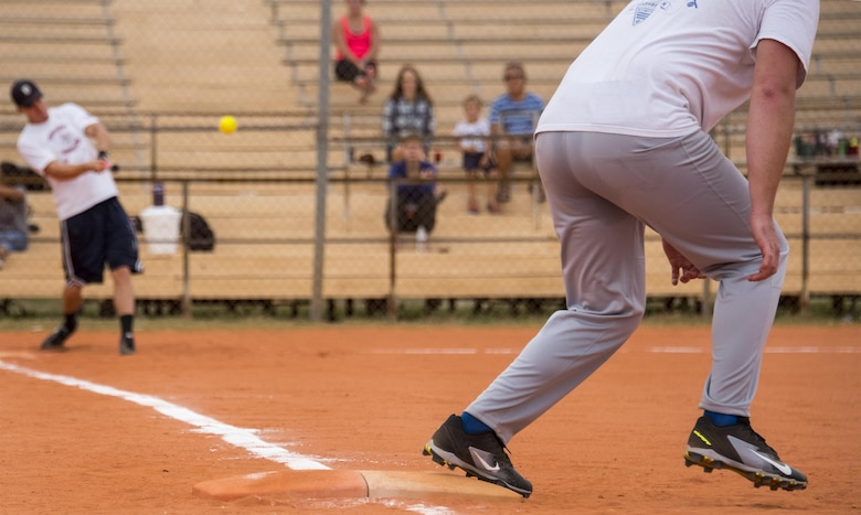 A 33rd Maintenance Group team member hits a line drive as the runner takes off from first base during their team's intramural softball game against the 96th Communications Squadron team at Eglin Air Force Base, Fla., May 11.  The CS team won easily over the MXG team during the opening week of the intramural softball season.  (U.S. Air Force photo/Samuel King Jr.)