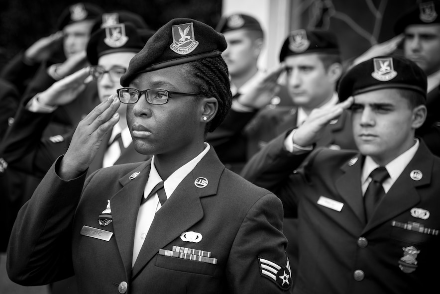 Senior Airman Delise Moore, 96th Security Forces Squadron, salutes with other Airmen in formation during the opening ceremony of Police Week at Eglin Air Force Base, Fla., May 15.  The ceremony was a gathering of security forces personnel for a formation and reveille ceremony performed at the All Wars Memorial.  Police Week activities will happen throughout the week and will close with security forces Airmen performing a retreat ceremony at Bldg. 1.  (U.S. Air Force photo/Samuel King Jr.)