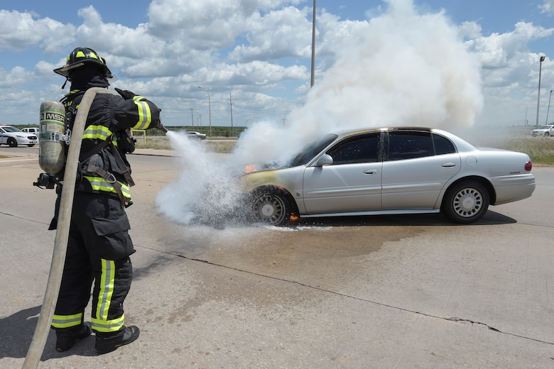 William Green, Tinker Fire and Emergency Services firefighter, sprays water on a vehicle which caught fire May 4, 2017, Tinker Air Force Base, Oklahoma. The privately owned vehicle developed mechanical trouble and caught fire near the Oklahoma City Air Logistics Complexs' building 9001. The fire was quickly and safely extinguished using water and powder while traffic was diverted to an alternate route as workers completed their shifts. Tinker Fire and Emergency Services is a division of the 72nd Civil Engineer Squadron. (U.S. Air Force photo/Greg L. Davis)