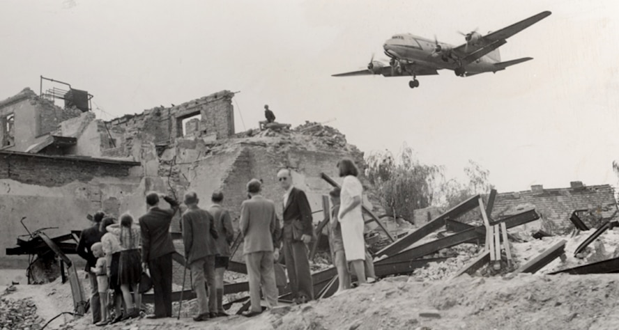 "United States Air Force Europe rounded up all of the C-47 Skytrains, affectionately called Gooney Birds, to fly cargo into West Berlin. One of the first to fly over was ""Operation Vittles"" as West Berliners wait in the rubble for supplies. (Courtesy photo)"
