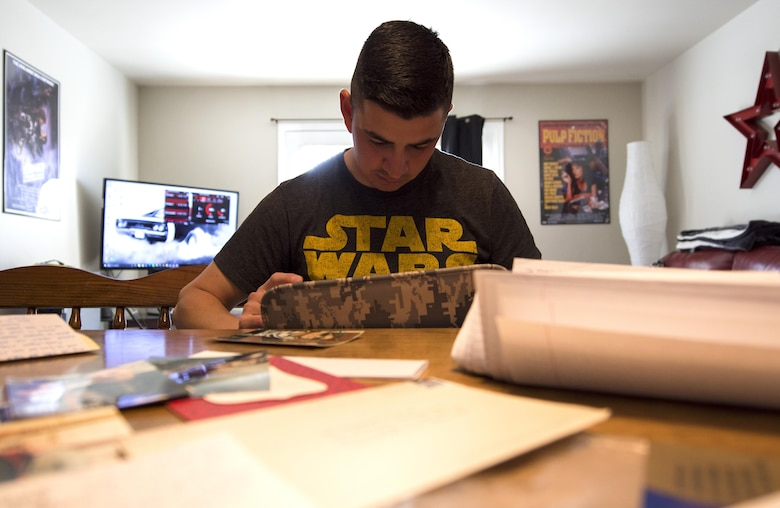 Airman 1st Class Jose Velazquez, U.S. Air Force Honor Guard firing party member, looks through old photos and letters from basic training in his home at Joint Base Anacostia-Bolling, District of Colombia, April 14, 2017. While achieving his goal of joining the military and gaining citizenship during Air Force basic training, Velazquez received mail from family and friends that he still holds onto. (U.S. Air Force photo by Senior Airman Philip Bryant)