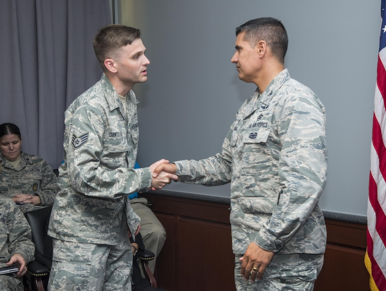 """Col. Eric Shafa, 42nd Air Base Wing commander, presents Staff Sgt. Robert Dantzler, 42nd Air Base Wing Public Affairs broadcast journalist, a commander's coin, May 15, 2017, Maxwell Air Force Base, Ala. Dantzler was awarded first place in the 2016 Defense Media Award's Video Feature Story category for his video """"Our Names on Her Arm."""" The video tells the story of the 455th Expeditionary Medical Group's mission to save the life and leg of a six year old girl who had been shot. Dantzler made the video while deployed at Bagram Airfield, Afghanistan. (U.S. Air Force photo/ Senior Airman Alexa Culbert)"""