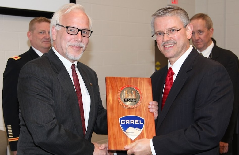 HANOVER, N.H. – Dr. Joseph L. Corriveau (left) takes the reins as he accepts the Cold Regions Research and Engineering Laboratory seal from U.S. Army Engineer Research and Development Center (ERDC) Director Dr. David W. Pittman (right) here May 15 ERDC Commander Col. Bryan S. Green (left rear) and out-going Director Dr. Robert E. Davis (right rear) were also key members of the transition ceremony.