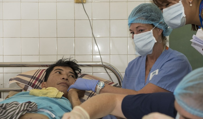 Christine Booth, Project Hope volunteer, comforts a burn victim receiving medical care from U.S. Navy doctors Vietnamese doctors at Da Nang General Hospital during Pacific Partnership 2017 Da Nang May 9. Pacific Partnership is the largest annual multilateral humanitarian assistance and disaster relief preparedness mission conducted in the Indo-Asia-Pacific and aims to enhance regional coordination in areas such as medical readiness and preparedness for manmade and natural disasters.