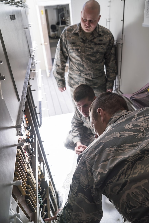 Tech. Sgt. Aaron Steinberg (bottom-right), 266th Range Squadron ground radar technician, shows the inner workings of the Multiple Threat Emitter System to Senior Airman Joshua Vance and Staff Sgt. Zachary Dowd at the Mountain Home Air Force Base Range Complex in Idaho May 9, 2017. Dowd, an Air Force Repair Enhancement Program technician, repaired a $20,000 power supply for the system, saving the Air Force thousands of dollars. (U.S. Air Force photo/Staff Sgt. Samuel Morse)