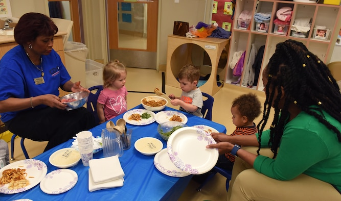 Two 9th Force Support Squadron child development center staff help care for a group of children during a spaghetti luncheon April 14, 2017, at Beale Air Force Base, California. When a recent hiring freeze came down, Beale's CDC experienced some staffing issues, but they were still able to provide child care with creative problem solving and help from their leadership. (U.S. Air Force photo/Chandresh Bhakta)