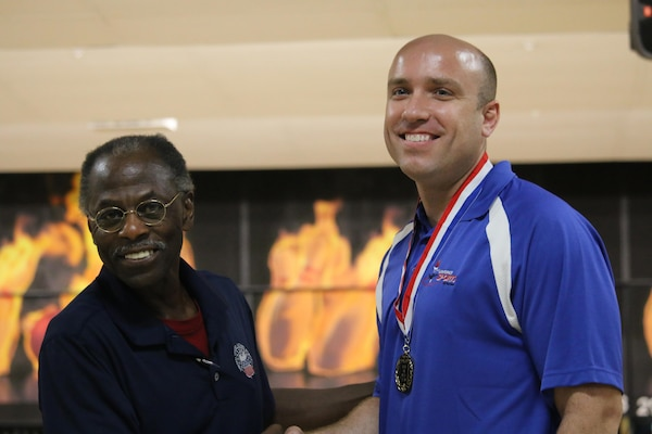 Armed Forces Sports Deputy Secretariat Mr. Ken Polk congratulates Air Force Staff Sgt. James McTaggart of Nellis AFB, Nevada for winning the Men's Title at the Armed Forces Bowling Championship hosted at Marine Corps Base Camp Pendleton, California from 5-8 May at the Leatherneck Lanes.