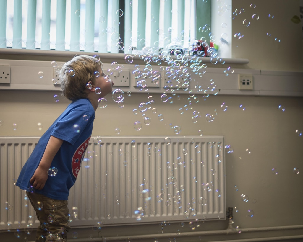 The son of a  U.S. Air Commando assigned to the 352d Special Operations Wing plays with a bubble machine during Roald Dahl day at the Preservation of the Force and Family building May 13, 2017 on RAF Mildenhall, England. The POTFF mission is to build and implement a holistic approach to address the pressure on military members and their families. This event was one of many regular 352 SOW programs which reinforce resilience techniques and methods for resolving challenges associated with special operations service. (U.S. Air Force photo by Capt Chris Sullivan)