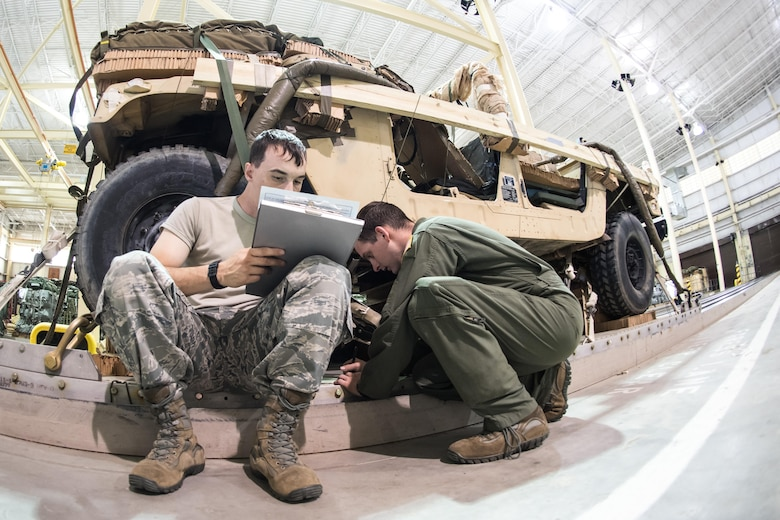 Staff Sgt. Matthew Van Compernolle and Senior Airman Wesley Zech, joint airdrop inspectors in the 43d Operations Support Squadron at Pope Army Airfield, complete paperwork to clear heavy equipment for airdrop after an inspection at the Army's Heavy Drop Rigging Facility here April 26. Van Compernolle and Zech worked with fellow 43d OSS inspectors to ensure more than 200 tons of cargo were ready for airdrop during Large Package Week and Exercise Jade Helm. (U.S. Air Force photo/Marc Barnes)