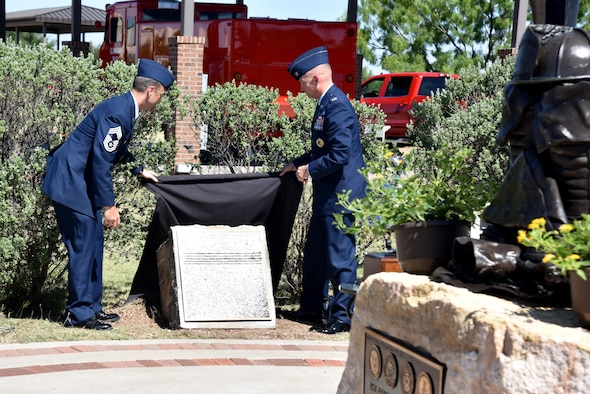 U.S. Air Force Chief Master Sgt. Scott Knupp, Air Force fire chief, and Col. Michael Downs, 17th Training Wing commander, unveil the plaque with the names of the five fallen firefighters honored at a memorial service at the Department of Defense Fallen Firefighter Memorial on Goodfellow Air Force Base, Texas, May 12, 2017. The plaque includes the two firefighters that died in the past two years and the three that died in Vietnam.  (U.S. Air Force photo by Staff Sgt. Joshua Edwards/Released)
