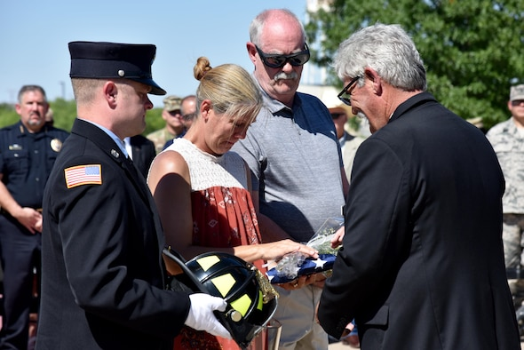 Mike Robertson, Military Firefighter Heritage Foundation president and executive director, hands Lore Long an American flag and a white rose for the loss of her husband during the Department of Defense Fallen Firefighter Memorial Ceremony on Goodfellow Air Force Base, Texas, May 12, 2017. Adam Long was one of the five firefighters honored. (U.S. Air Force photo by Staff Sgt. Joshua Edwards/Released)
